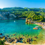 Why is it important for every traveler to Corfu to visit the beautiful village of Paleokastritsa?